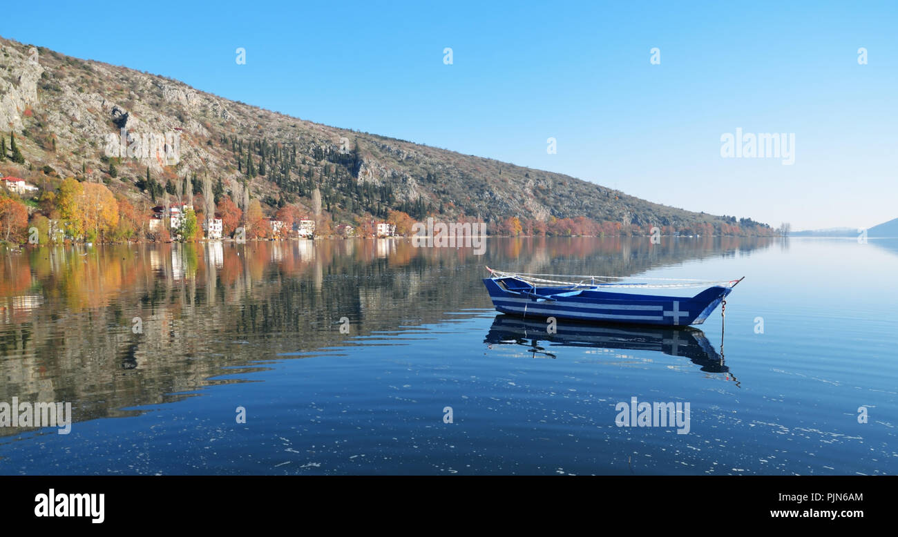 A kastorian traditional fishing boat, with greek flag painted on it, floating in calm waters on a autumn day - Stock Image