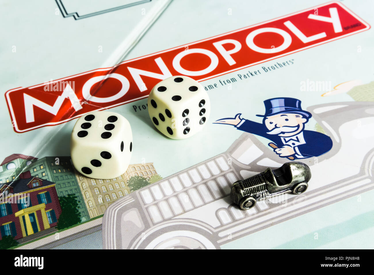 Monopoly Board Game close up with the box, board and dices. The classic real estate trading game from Parker Brothers - Stock Image