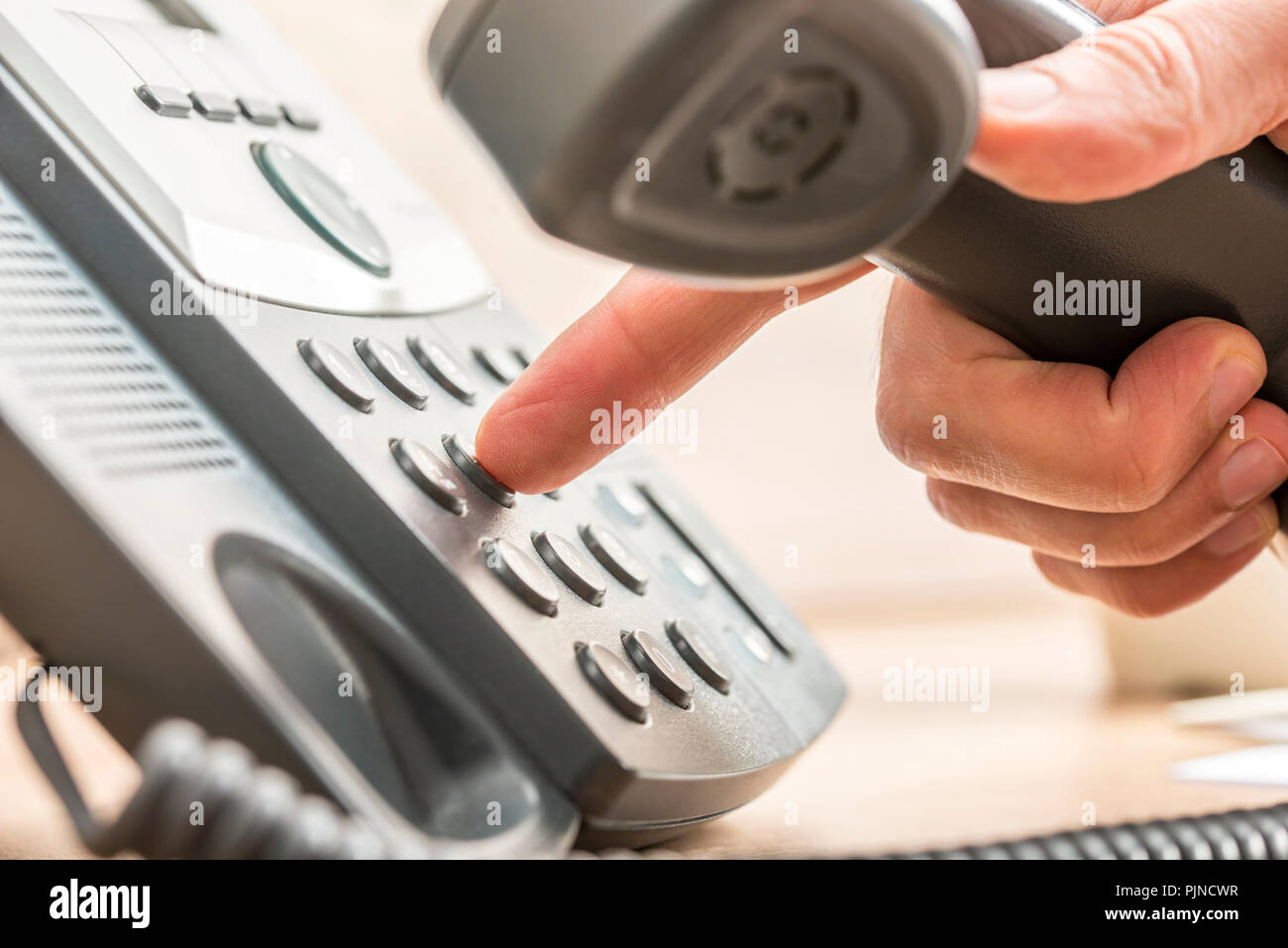 Closeup of male telemarketing salesperson holding a telephone receiver dialing phone number to make a business call. - Stock Image