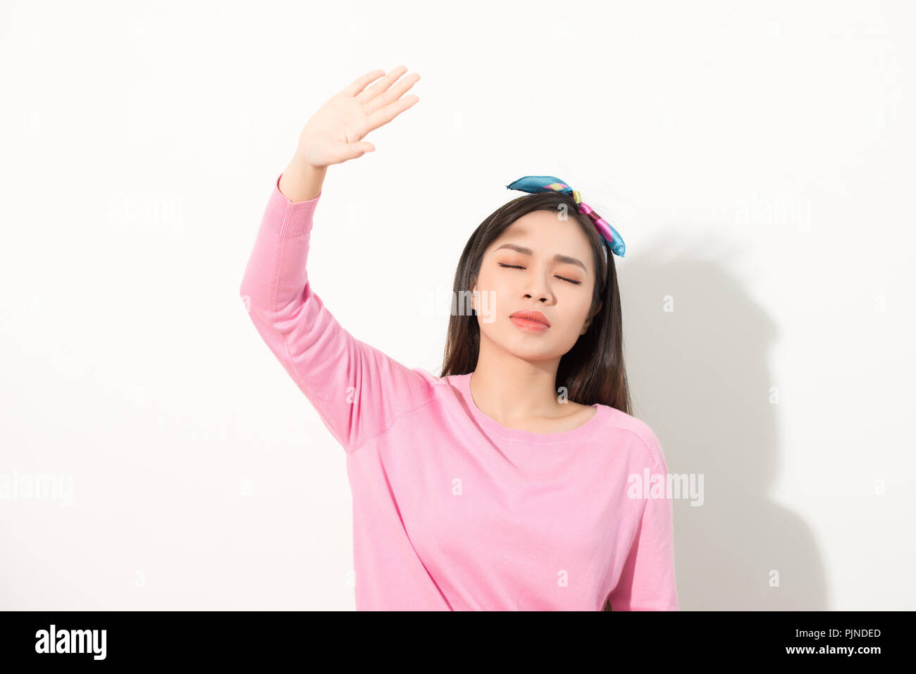 Portrait of a beautiful Asian girl covering face by hand of bright sun light. woman in a pink dress protecting her face from solar light. Skin care or - Stock Image