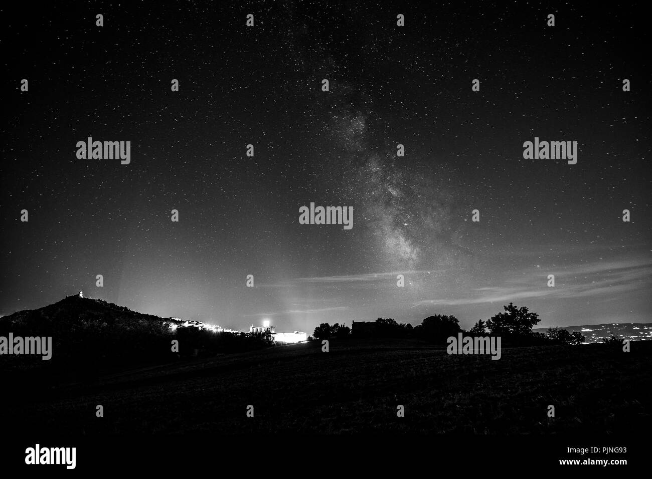 beautiful view of starred night sky with milky way over a cultivated field assisi town umbria italy in the background PJNG93