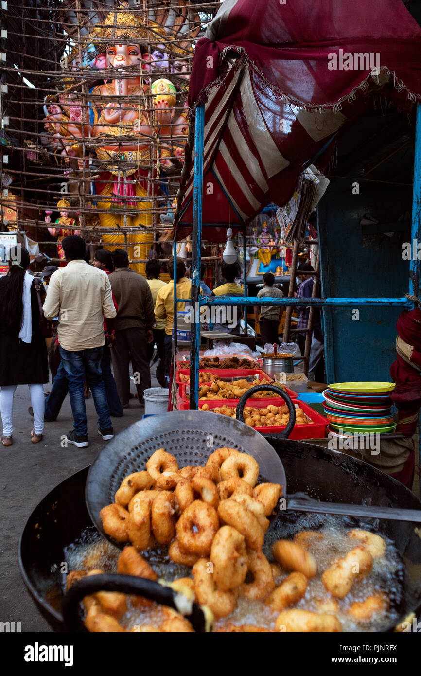 Hyderabad,India. 08th September,2018.A street vendor prepares snacks in front  of 57 feet tall idol of Lord Ganesh popularly known as Khairatabad Ganesh in southern city of Hyderabad, ahead of Ganesh Chaturthi festival which begins on September 13,2018.  Ganesh Chaturthi is a 10-day Hindu festival celebrated throughout India marking the birth of the elephant-headed god Lord Ganesha, the god of prosperity and wisdom.Credit:Sanjay Borra/Alamy Live News. Stock Photo