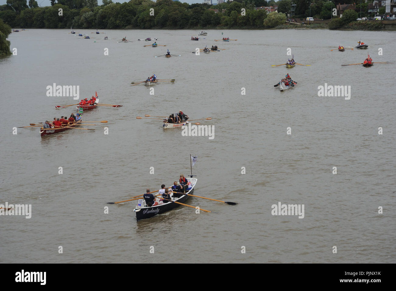 Competitors enjoy the camaraderie and competition in the Thames Great River Race, viewed from Barnes Bridge, SW13. - Stock Image