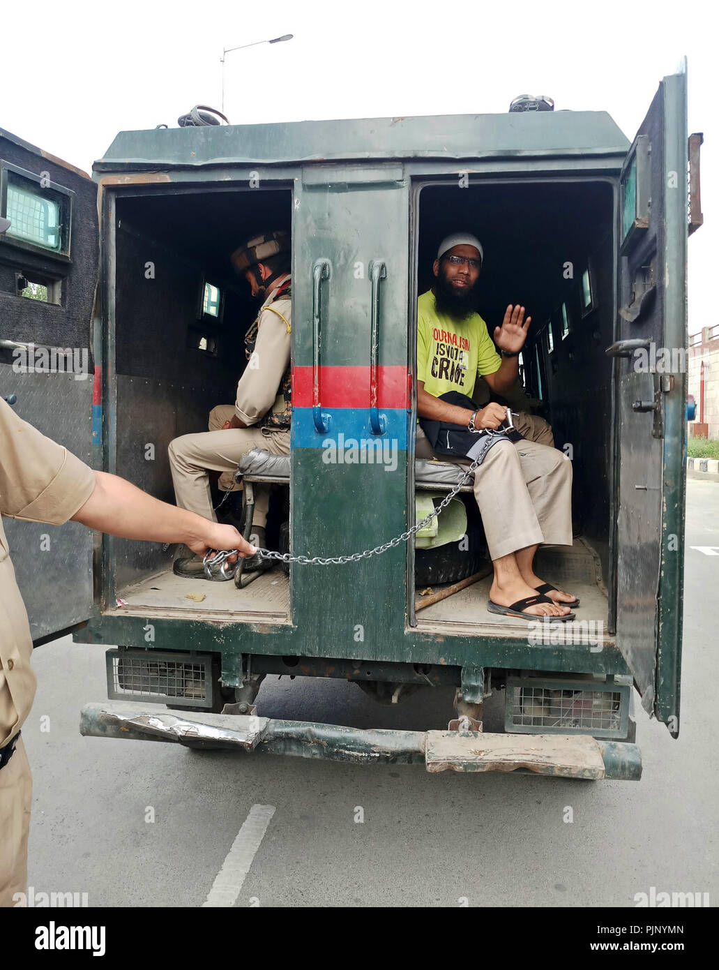 Srinagar, J&K, India. 8th Sept, 2018. - Aasif Sultan seen waving to his relatives from the police vehicle outside the court.Aasif Sultan, a local journalist and Assistant Editor of Kashmir Narrator magazine was arrested by the government forces and now being sent to Central Jail in judicial custody until Sept 22. He was arrested after a six-day detention at a police station in Batmaloo area of Srinagar.Several journalists' bodies including Reporters without Borders and International Federation of Journalists have called for his immediate release. (Credit Image: © Saqib Majeed/SOPA Image - Stock Image
