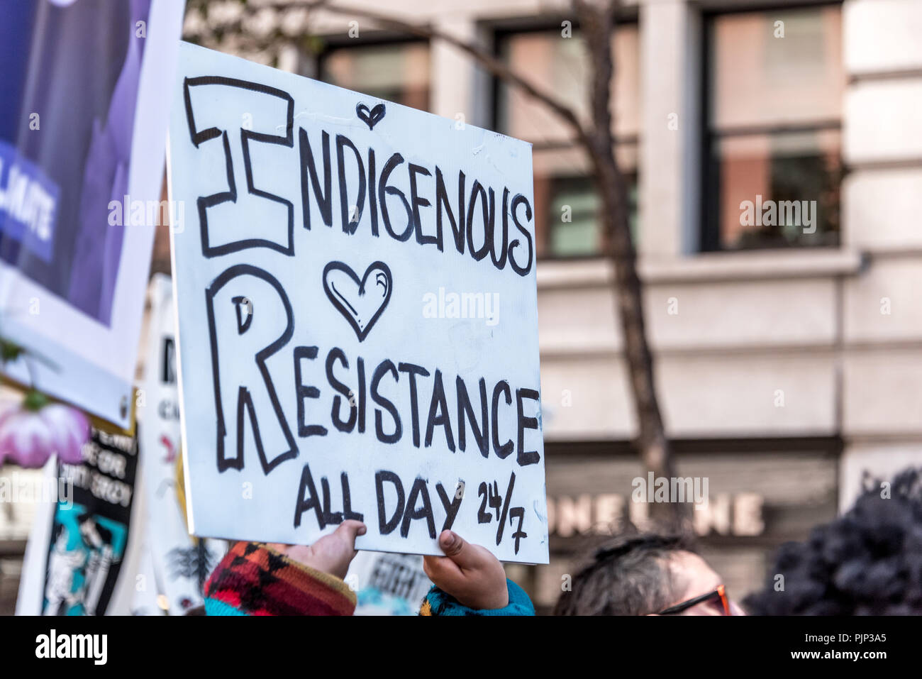 San Francisco, California, USA. 8th September, 2018. Thousands gather in San Francisco in Rise for Climate rally and march in advance of the Global Climate Action Summit to be held there September 12 to 14. A sign held above the crowd reads, 'Indigenous resistance all day 24/7.' Shelly Rivoli/Alamy Live News - Stock Image