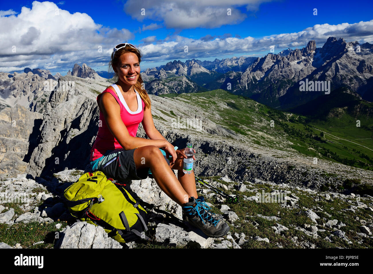 Young female hiker pauses during the ascent from the Prato Piazza to the summit of the Dürrenstein, in the background Monte - Stock Image