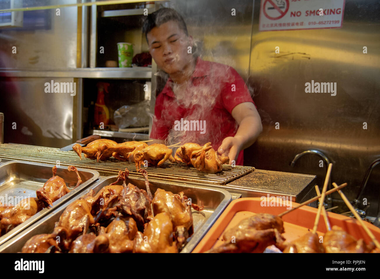 Beijing, China – June 1 2018: Chef in his red uniform cooking traditional Chinese  food on snack street at Beijing city in China - Stock Image