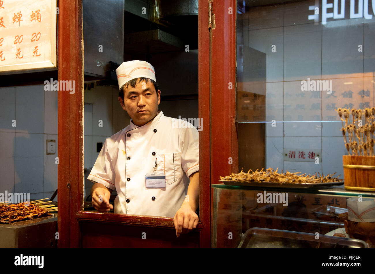 Beijing, China – June 1 2018: Chef in his white uniform cooking traditional Chinese  food on Snack street food market at Beijing in China - Stock Image