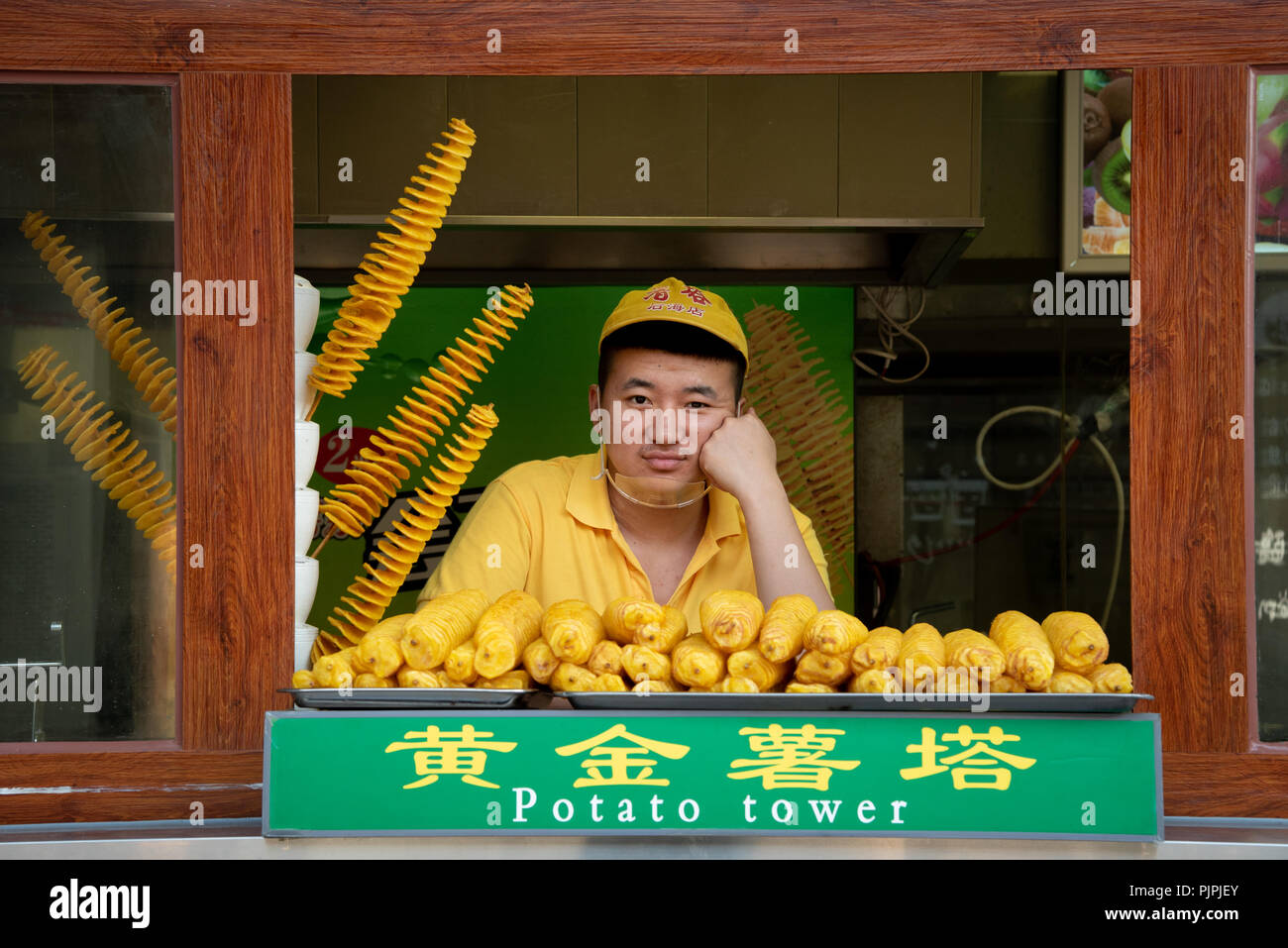 Beijing, China – June 6 2018: Chef in a yellow uniform selling  traditional Chinese  food on a streetmarket at Beijing in China - Stock Image