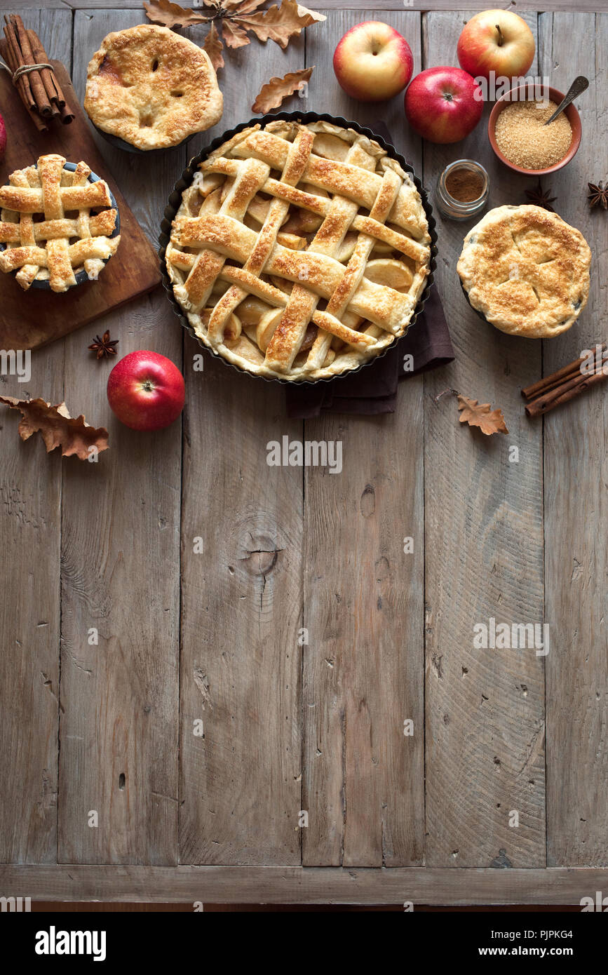 Homemade Apple Pies on rustic background, top view, copy space. Classic autumn Thanksgiving dessert - organic apple pie. - Stock Image