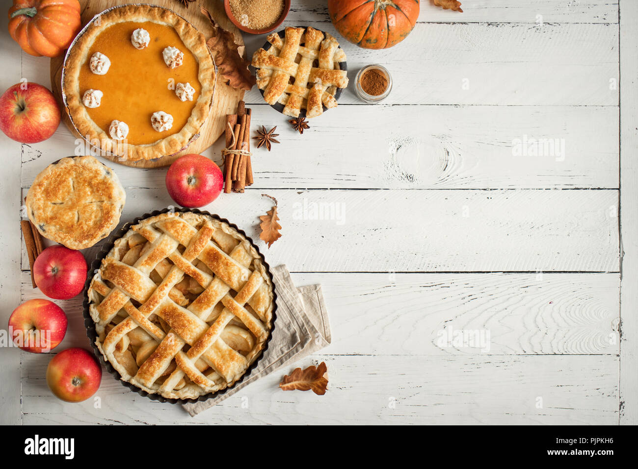 Thanksgiving pumpkin and apple various pies on white, top view, copy space. Fall traditional homemade apple and pumpkin pie for autumn holiday. Stock Photo