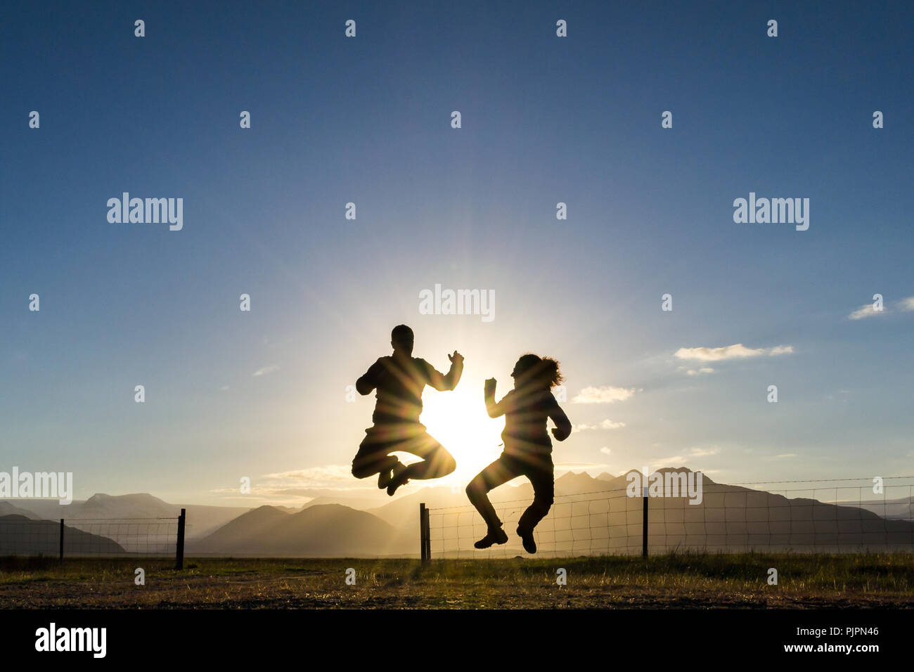 Two people jumping for fun near Hofn, Iceland, at sunset. Backlit silhouettes with some clouds and blue sky. Sensation of freedom and carelessness. - Stock Image