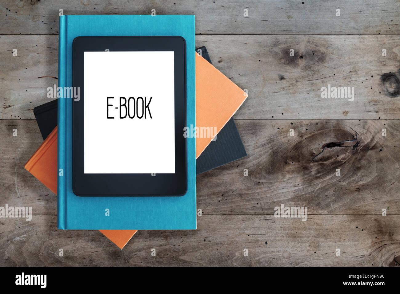 e-book reader on a stack of books on rustic wooden table concept - Stock Image
