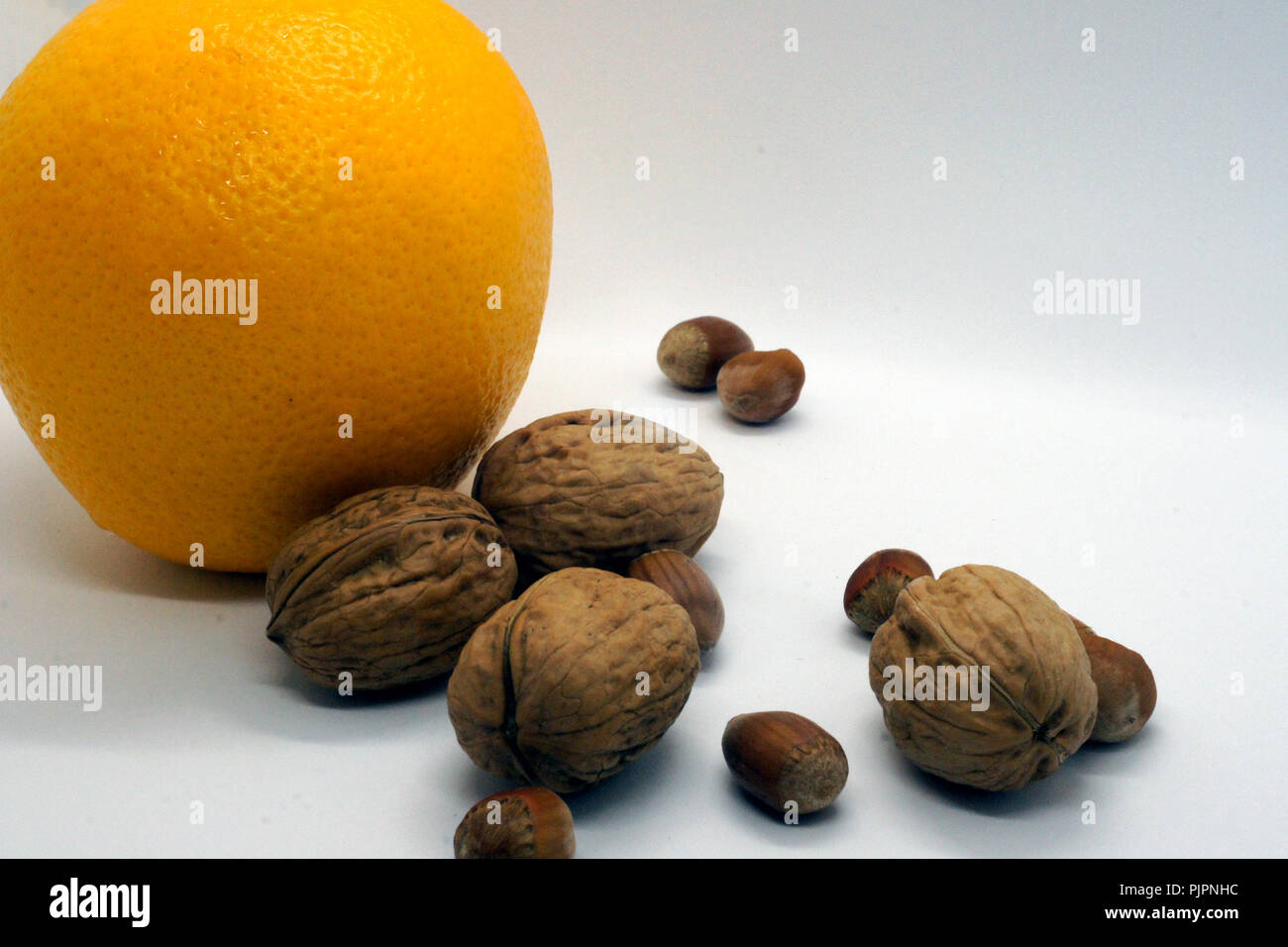 walnuts hazelnuts and orange - Stock Image