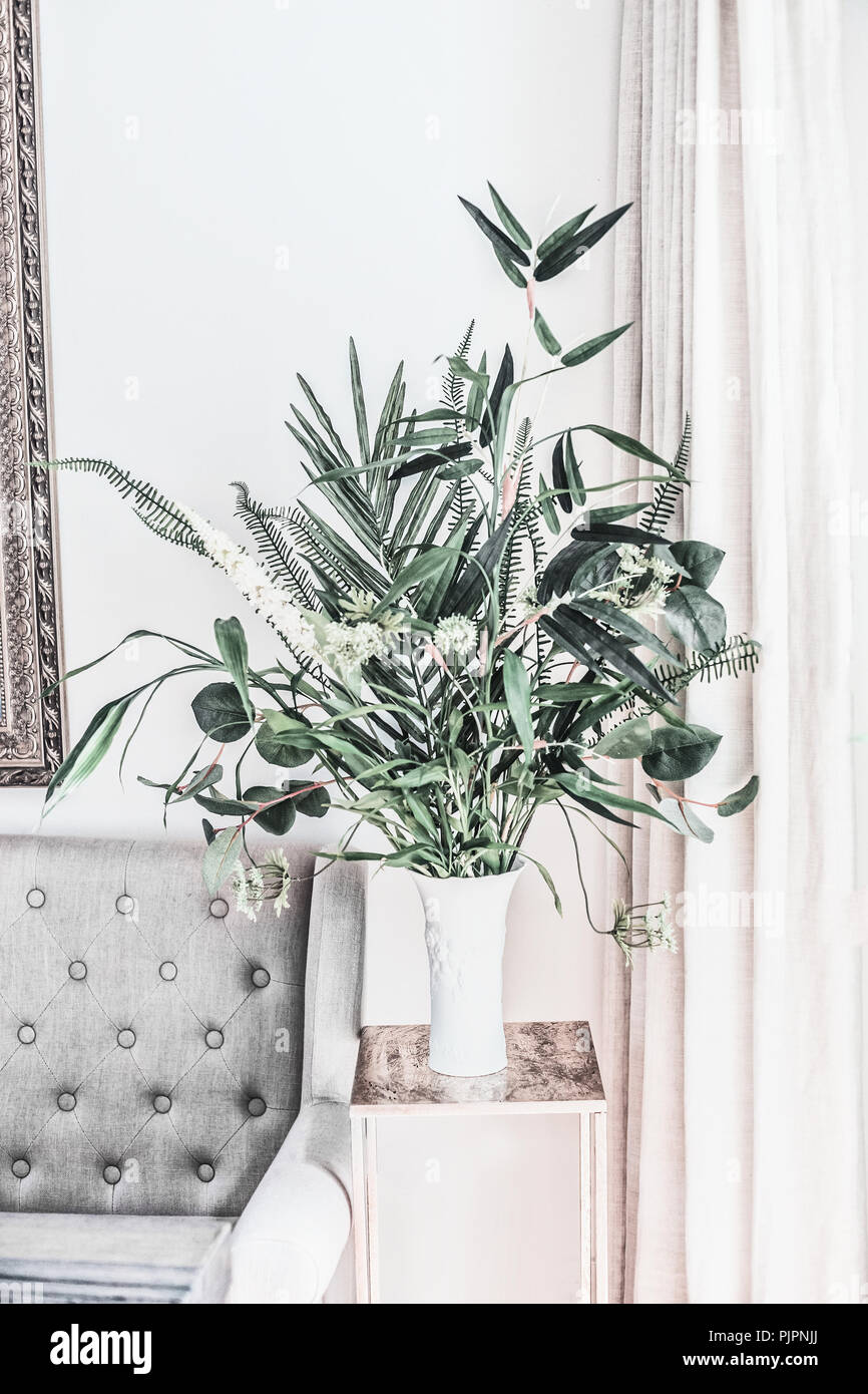 . Modern still life with house plants in vase at sofa  front view