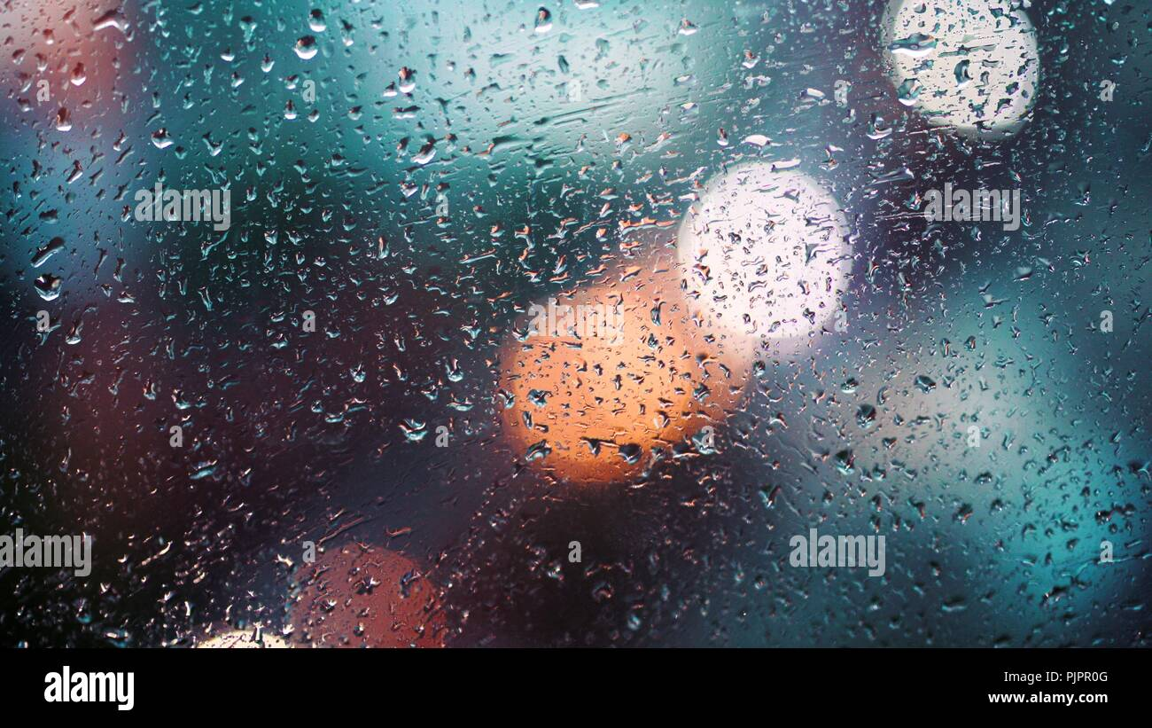 Close up view of water drops falling on glass. Rain running down on window. Rainy season, autumn. Raindrops trickle down, grey sky. - Stock Image