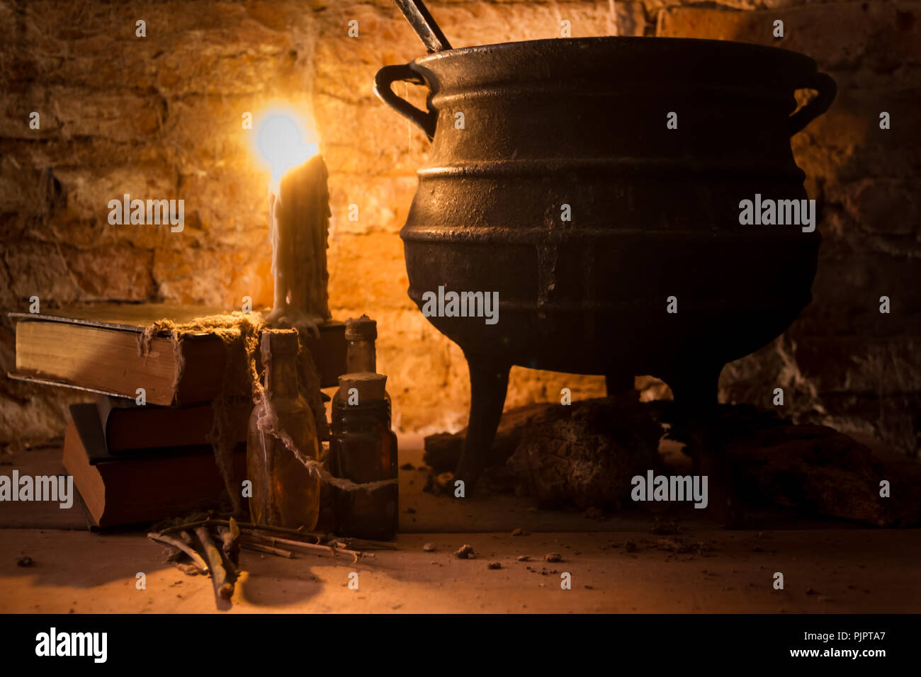 spell of witch night with candles and pot with fire between cobwebs and ancient earth - Stock Image