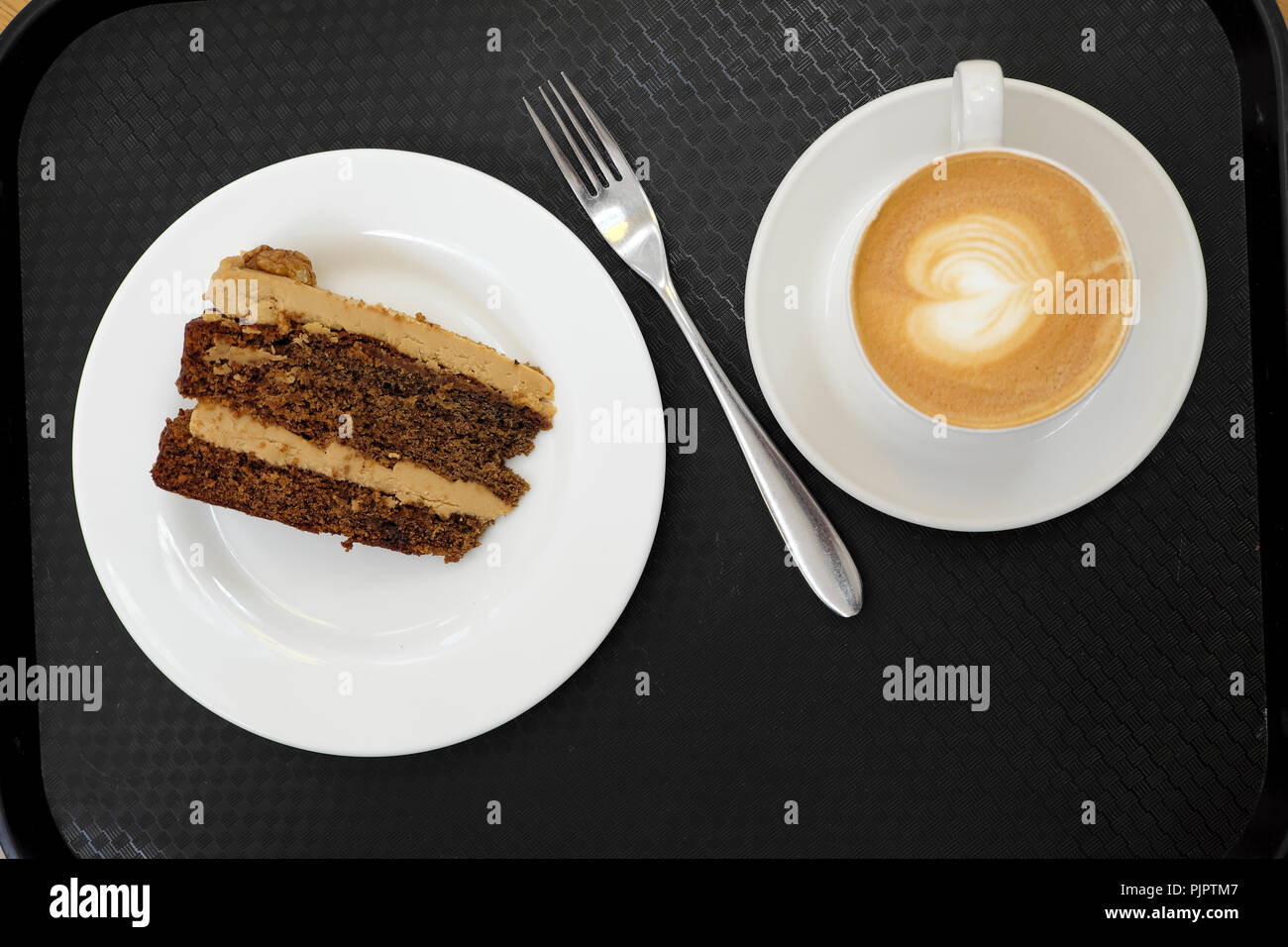 Overhead view of a cup of frothy milky coffee with heart shaped design, fork, chocolate walnut cake on black background in London UK  KATHY DEWITT - Stock Image