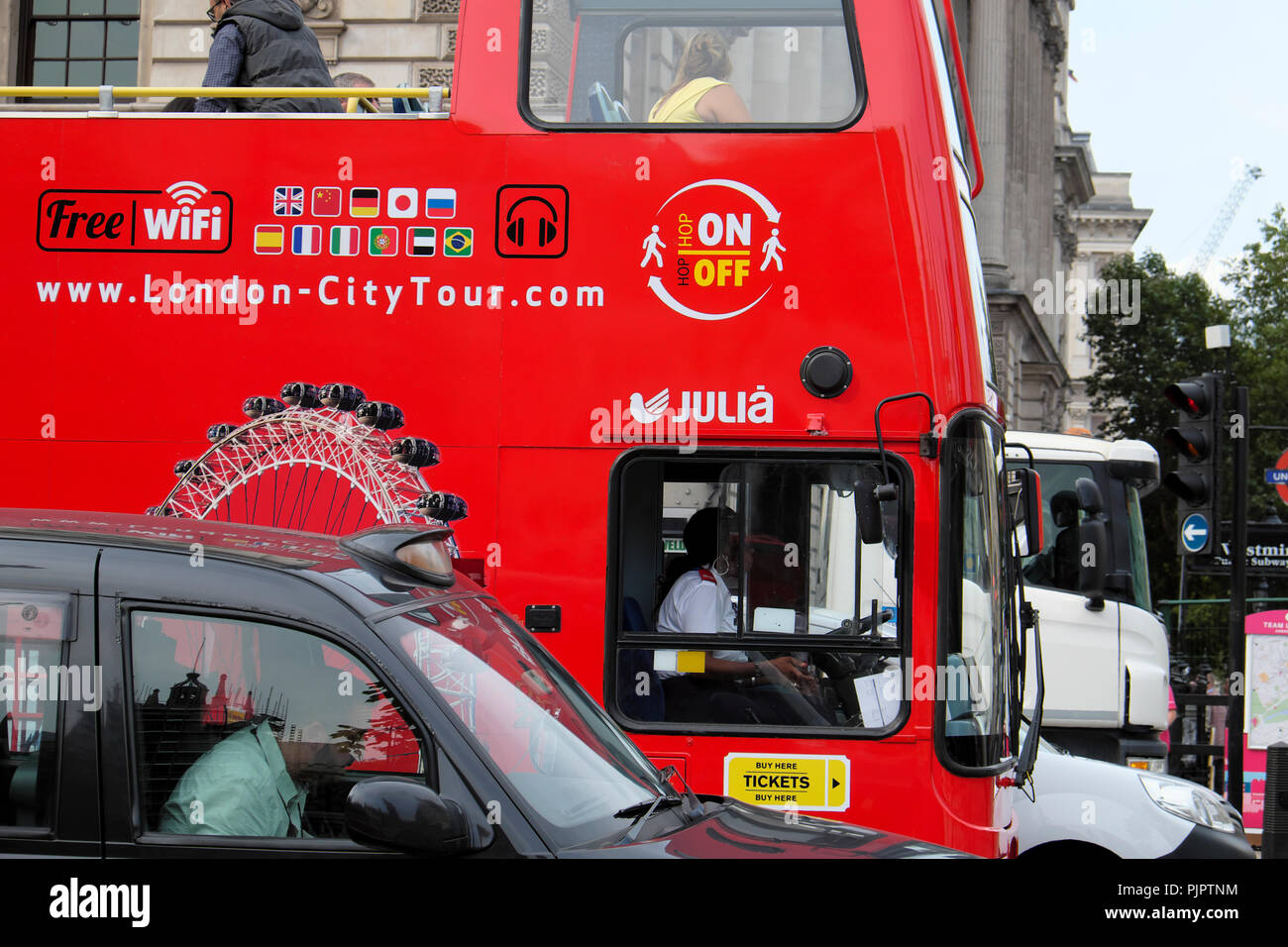 Red double-decker hop on - hop off City Tour tourist bus and driver stuck in Parliament Square traffic in City of Westminster London UK  KATHY DEWITT - Stock Image