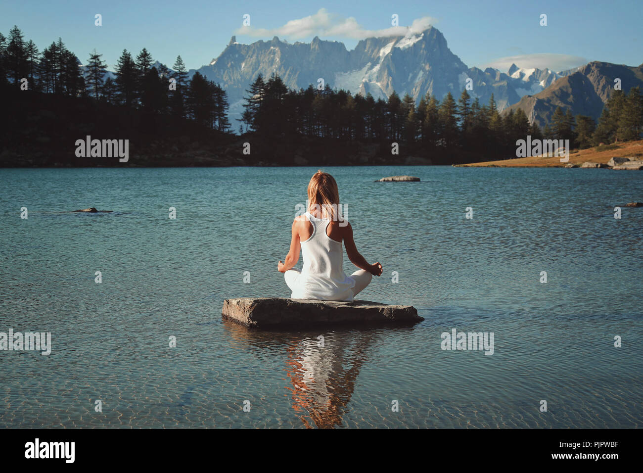 Woman meditation in mountain lake. Lotus asana - Stock Image