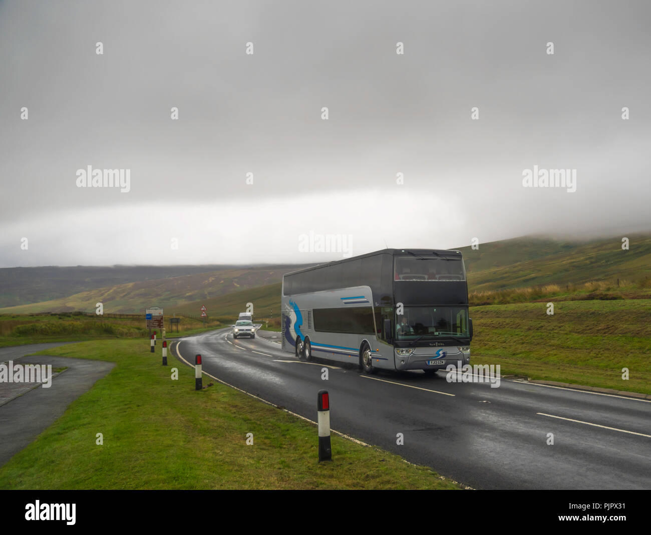 A Luxury Coach approaching the Scottish Border from England at Carter Bar on the A68 road in wet rainy adverse conditions - Stock Image