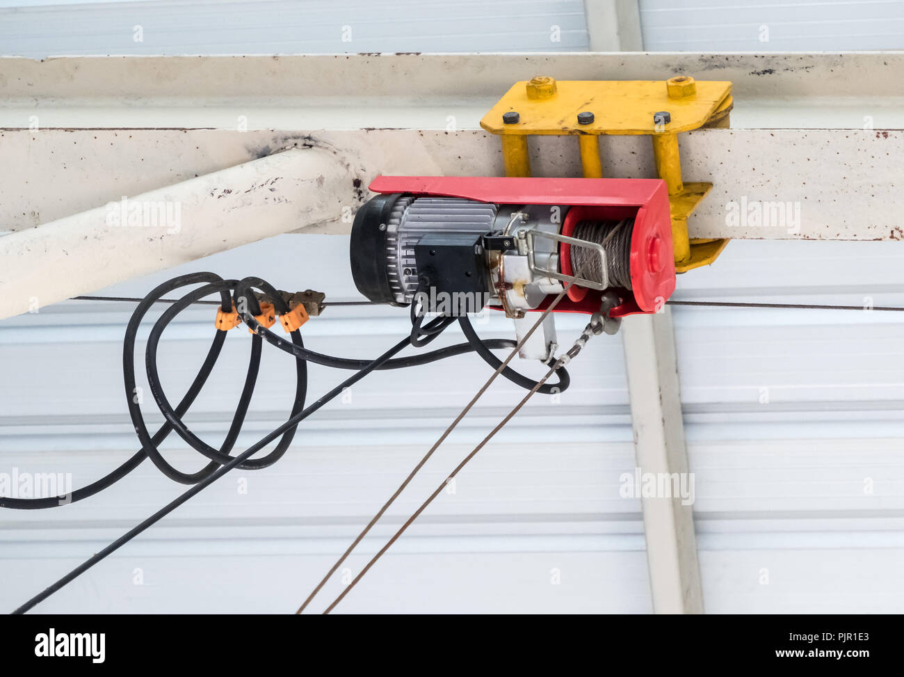 Small electric winch is installing on the ceiling frame of the ...