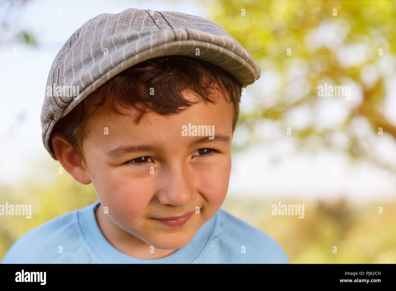 Child kid little boy portrait outdoor copyspace looking to the side with cap nature - Stock Image
