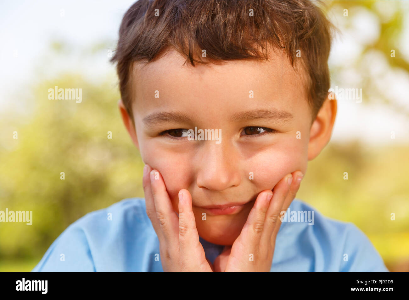 Child kid little boy thinking looking sorrow worry outdoor copyspace copy space outdoors outside nature - Stock Image
