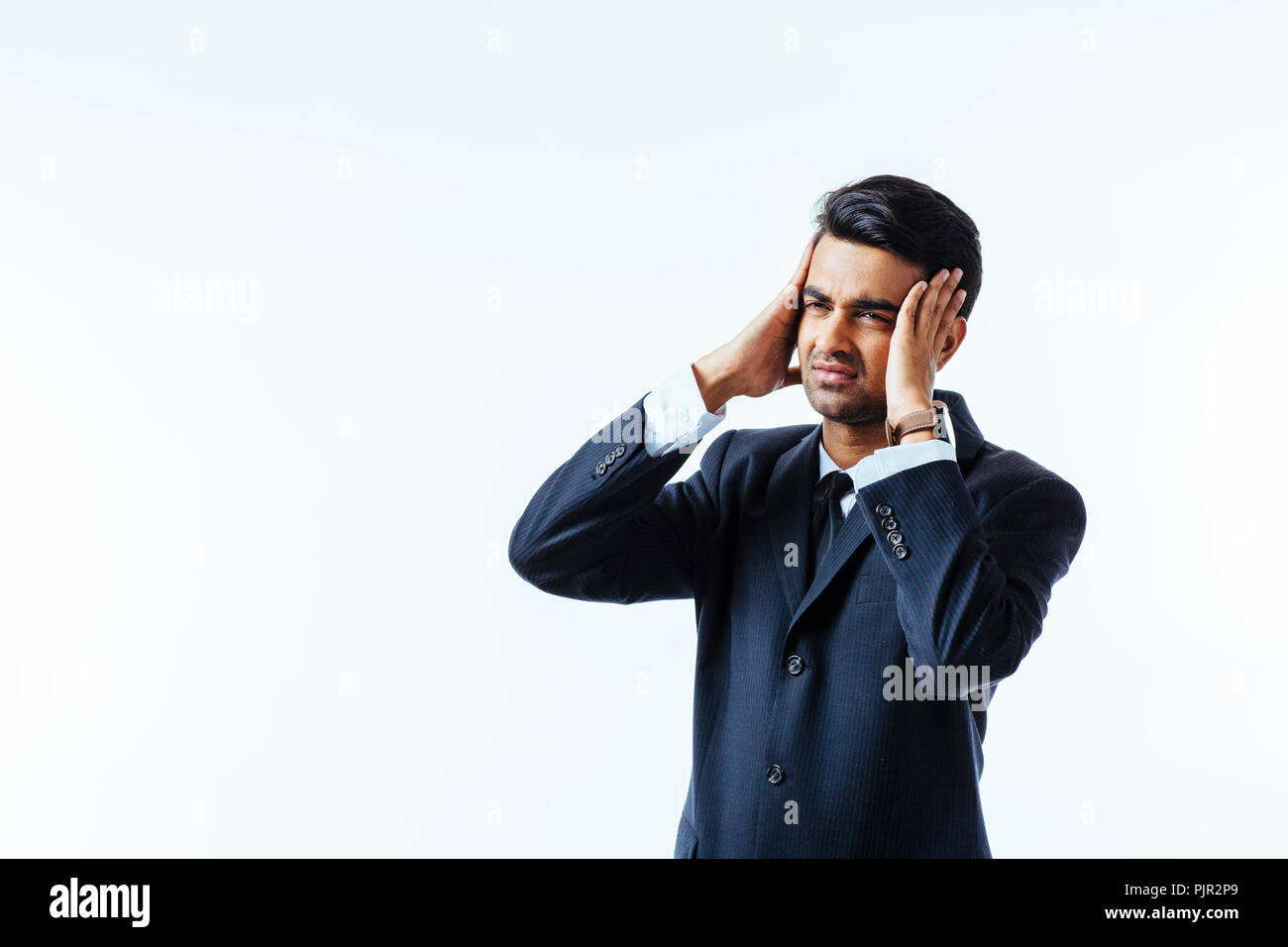 Portrait of a cool businessman  holding his head in disbelief or in pain, isolated on white background - Stock Image