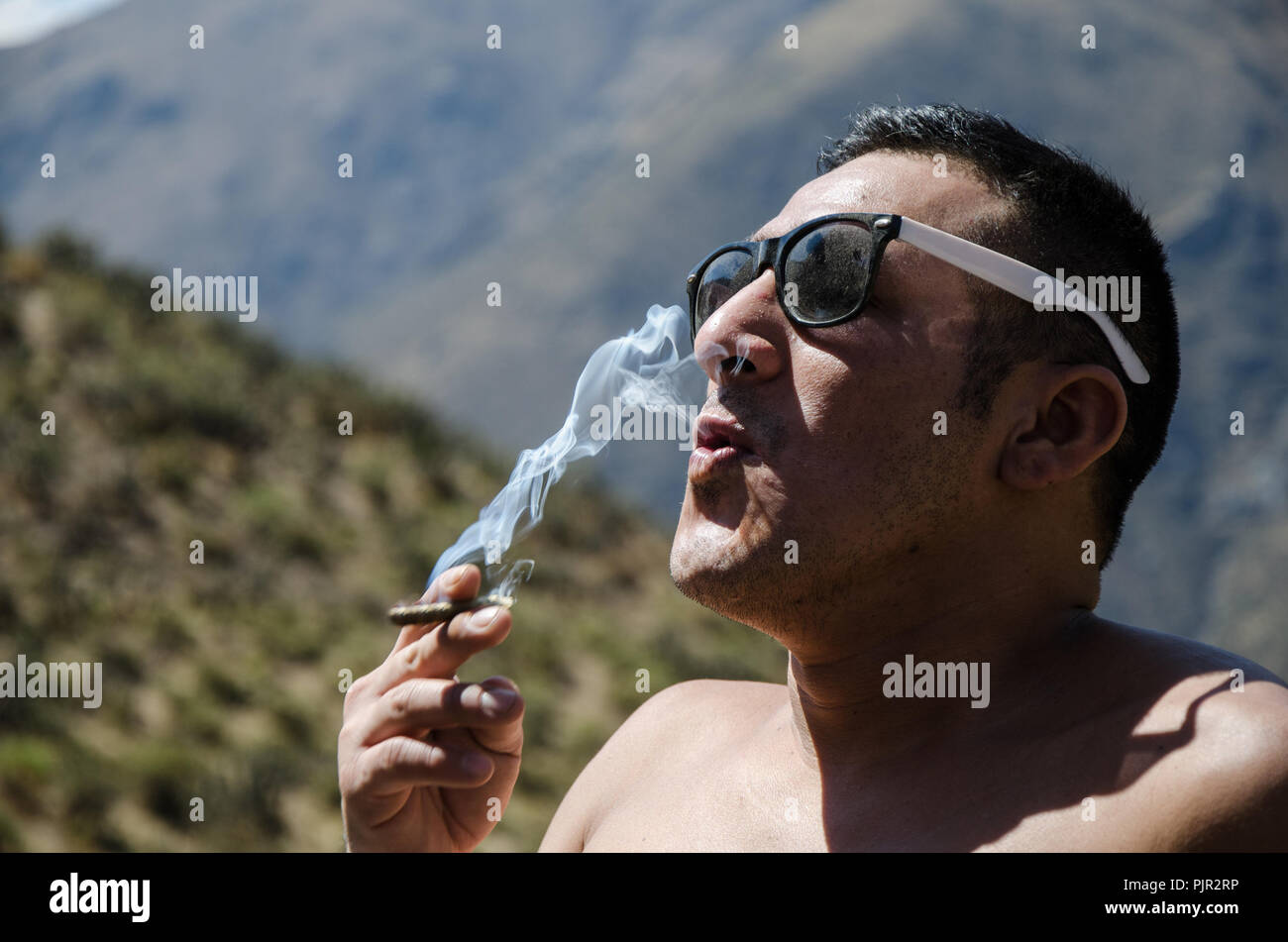 Young man smoking tobacco, man with sunglasses and mountains background - Stock Image