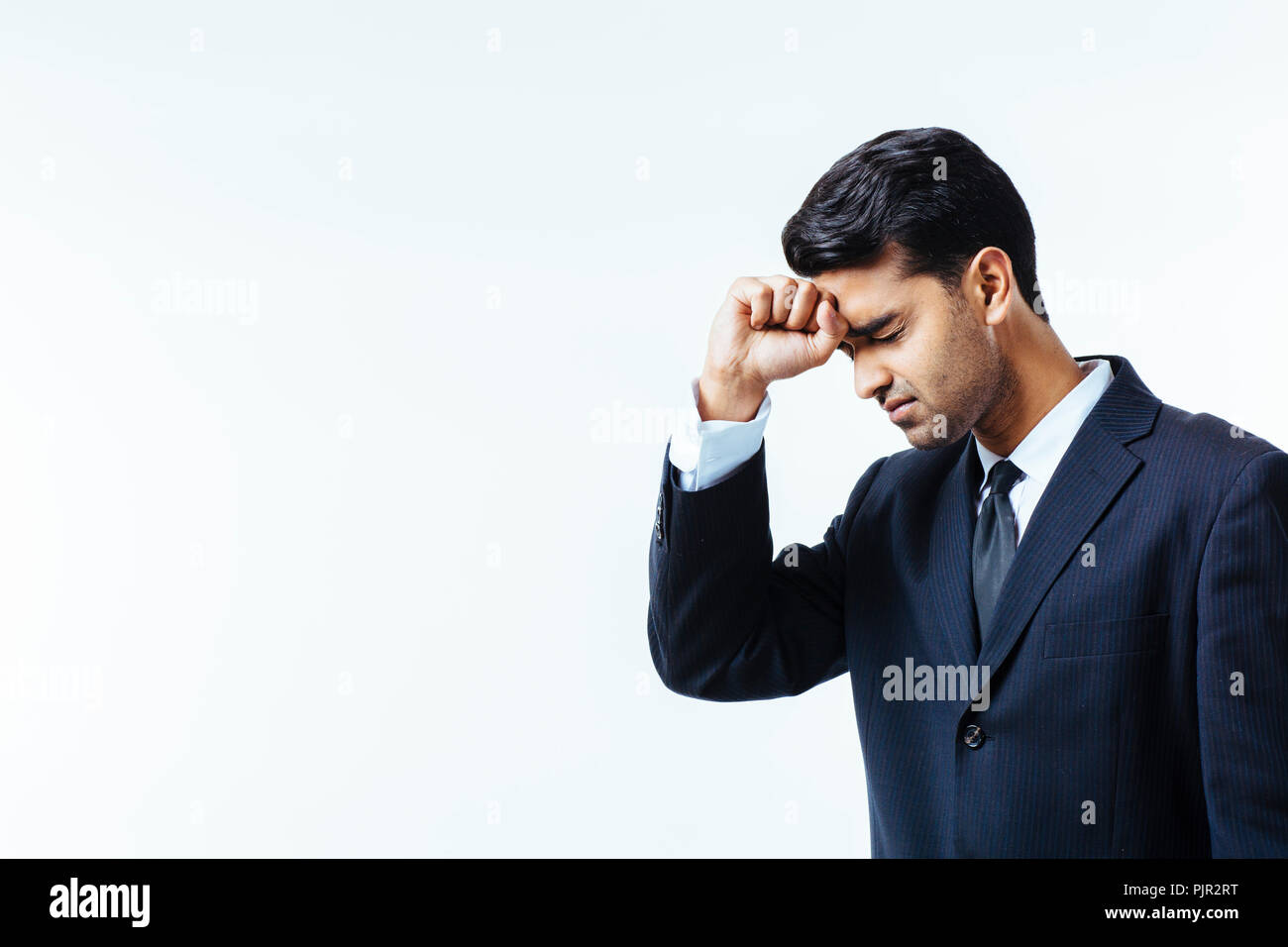 Portrait of a handsome businessman holding his head in disbelief, in pain or meditating,  isolated on white background - Stock Image