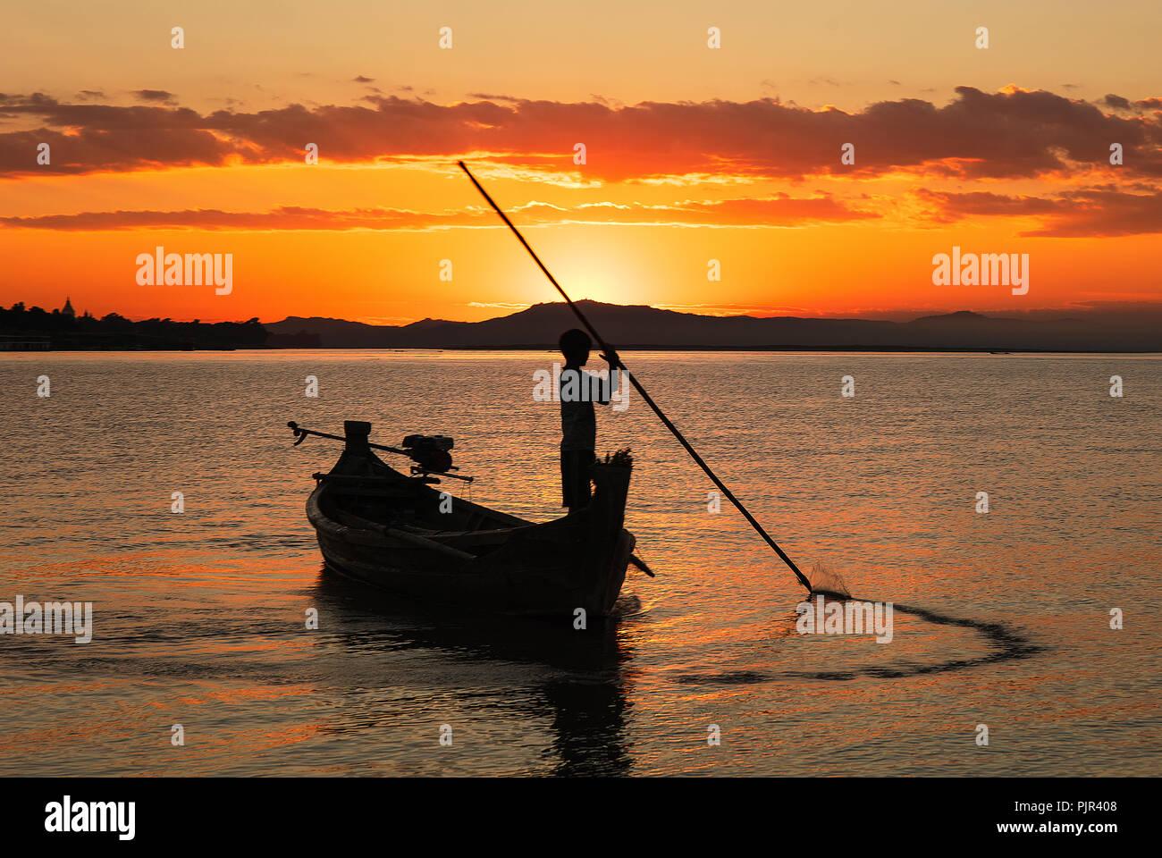 Silhouette of a youn fisherman on the Irrawaddy river at sunset, Nyaung U, Bagan, Myanmar (Burma). Stock Photo
