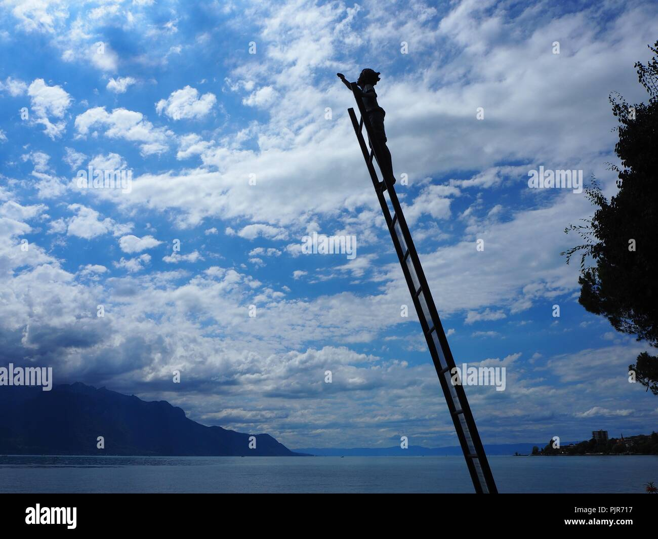 Montreux, Switzerland - Lake side, statue showing boy climbing a ladder to reach the sky - Stock Image