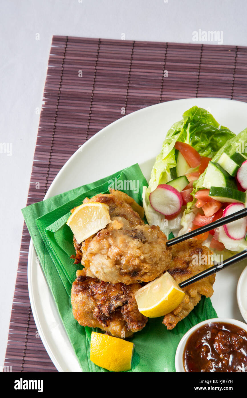 A plated meal of Chicken Karaage with red chili bean dip and Paprika yogurt served with a fresh mixed salad - Stock Image