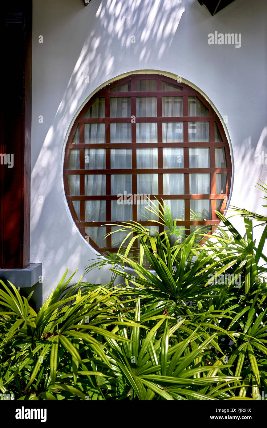 japanese window wood paned circular window set in a white wall home exterior PJR9K6