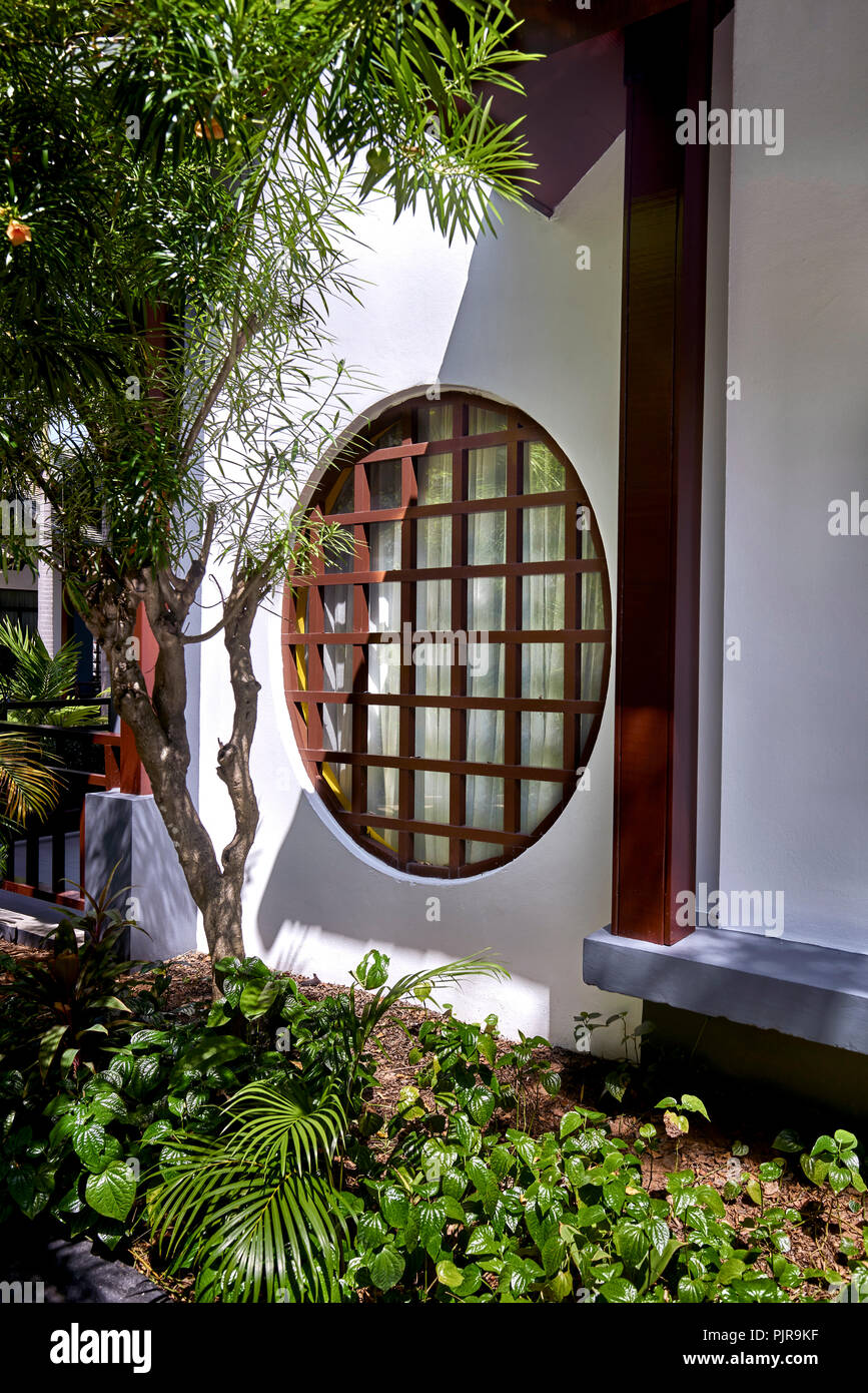 japanese wood paned circular window set in a white wall home exterior PJR9KF