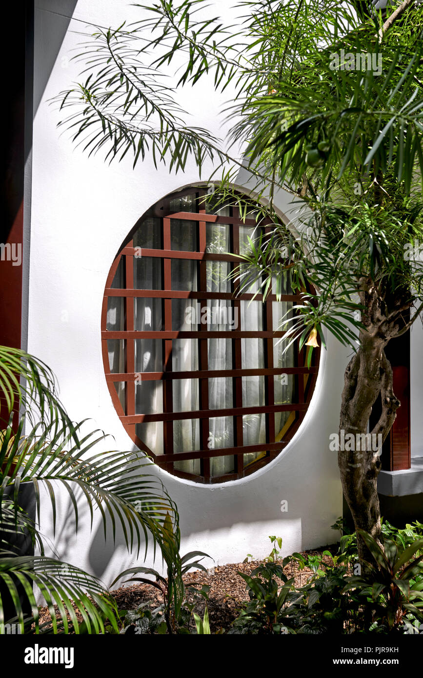japanese window wood paned circular window set in a white wall home exterior PJR9KH