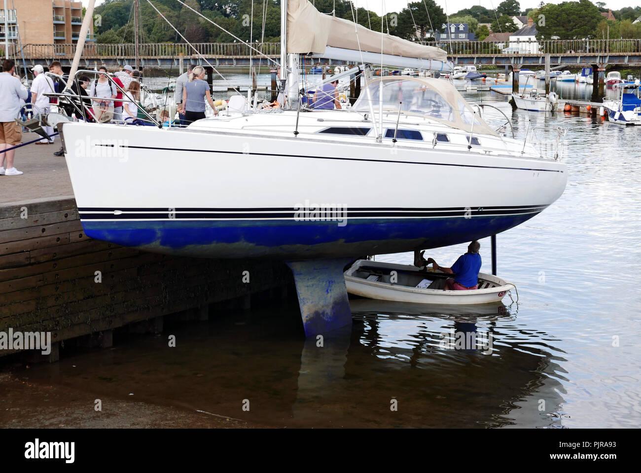 Man at Lymington harbour repairing underside of Yacht Stock Photo