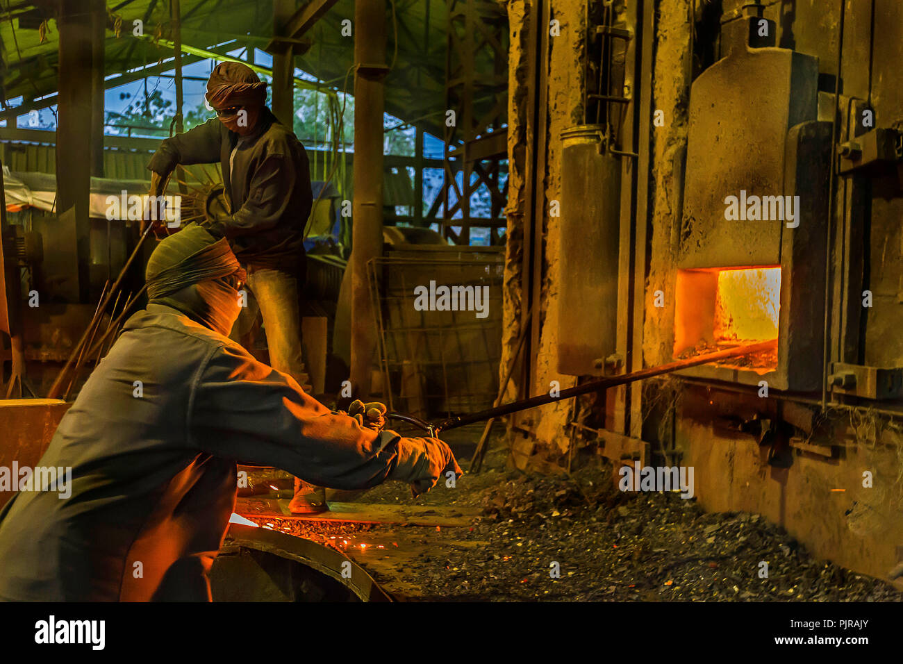 Indian industrial workers working hard in tough situation in foundry. - Stock Image
