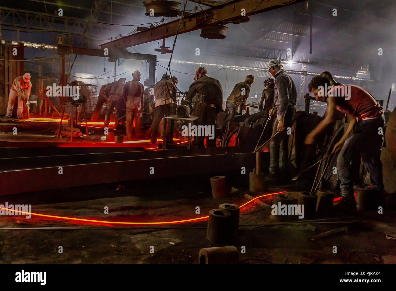 Indian industrial workers working hard in tough situation in foundry. Stock Photo