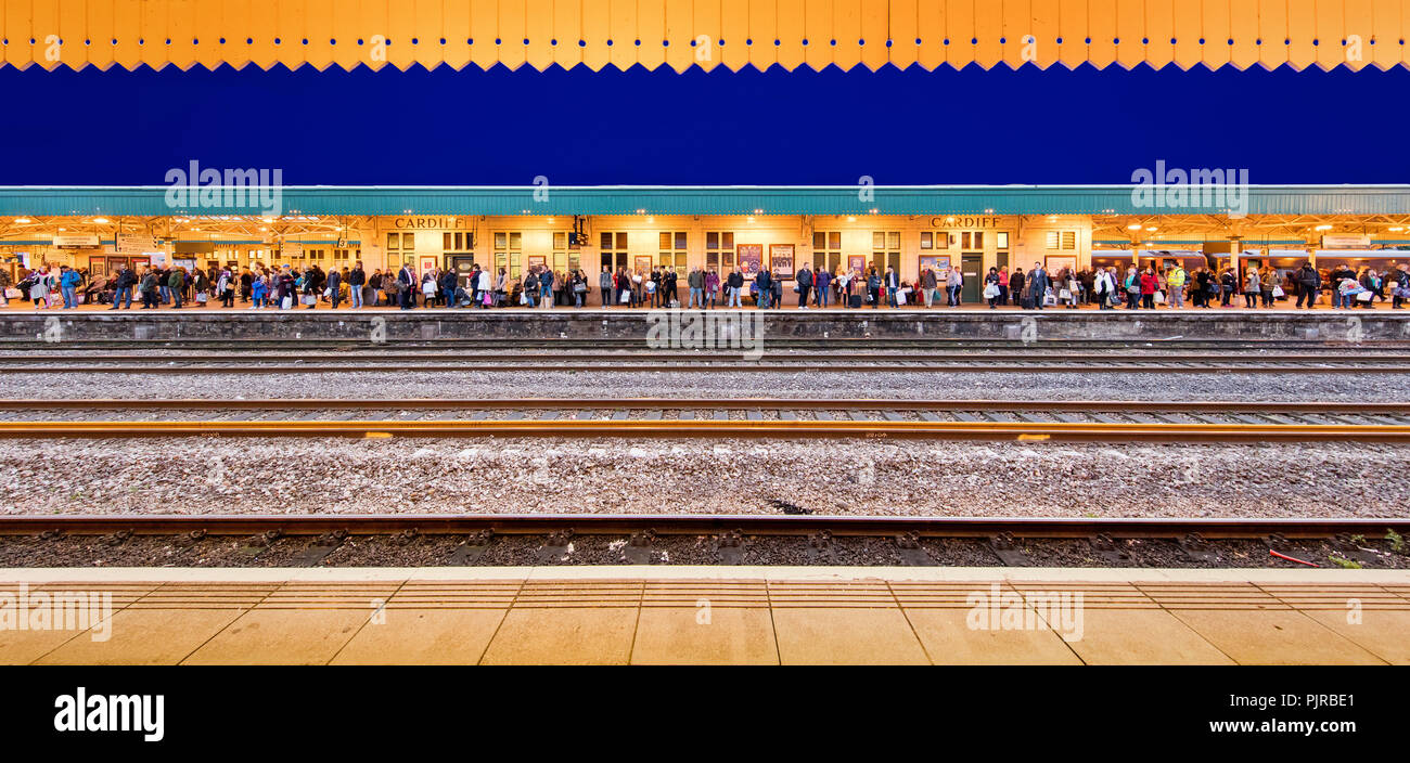 Cardiff station commuters waiting for a train on a winter's evening - super wideangle view - Stock Image