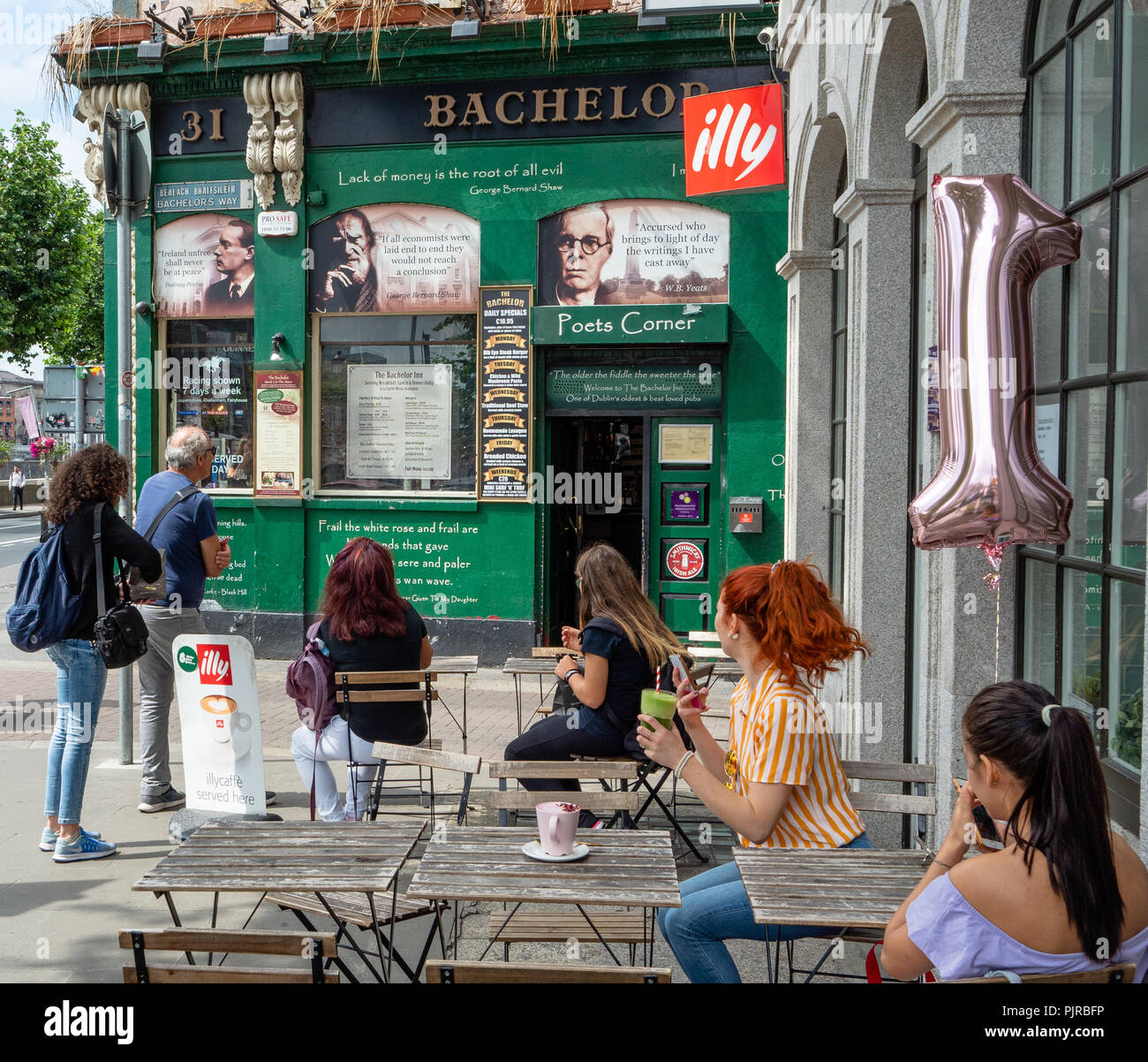 Readers of the literary content by writers and poets on the face of the Bachelor Inn on Bachelors Walk Quay by the River Liffey in Dublin Ireland - Stock Image