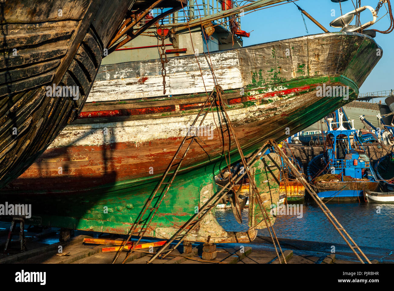 The stern of an old fishing boat under repair on a dock at the port of Essaouira in Morocco - Stock Image
