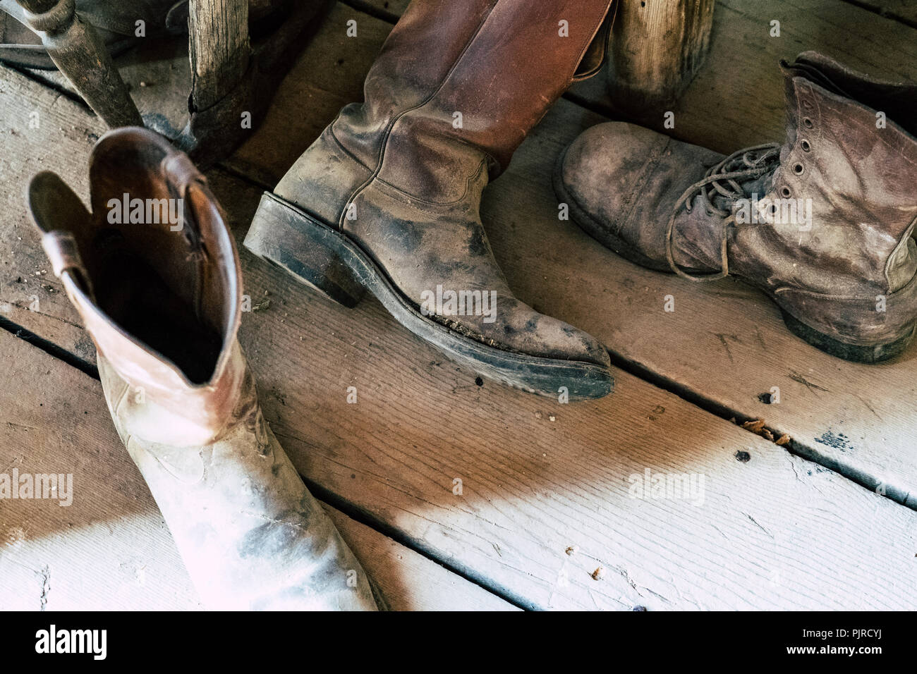 Old abandoned vintage cowboy boots sit on a dusty wooden plank floor. Selective focus for artistic purposes Stock Photo