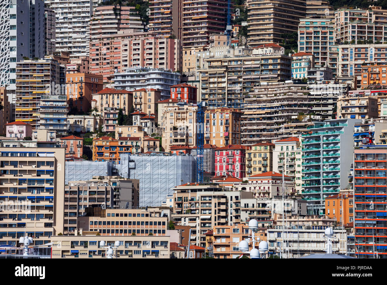 Principality of Monaco cityscape, densely populated urban background on mountain slope with houses, apartment buildings, towers, block of flats Stock Photo