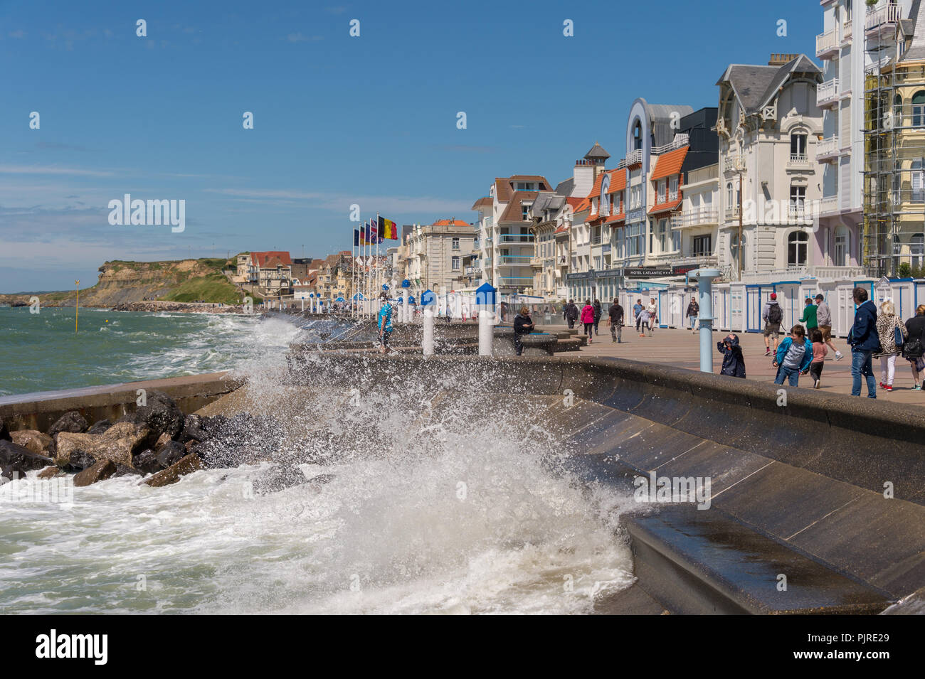Wimereux, France - 16 June 2018: People walking on the sea front promenade as waves are hitting the sea wall. - Stock Image