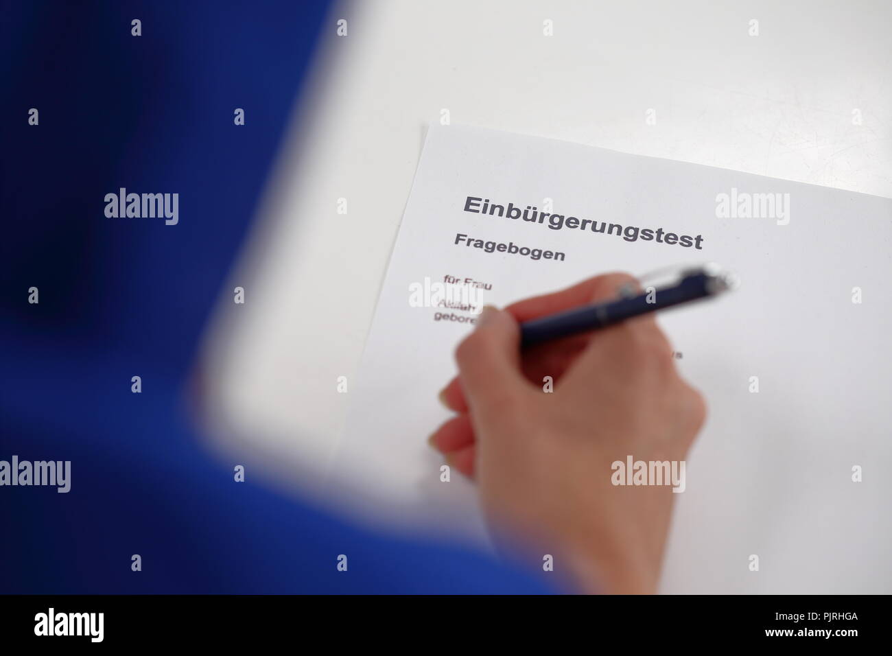 A Woman filling out a german Citizenship test - Stock Image