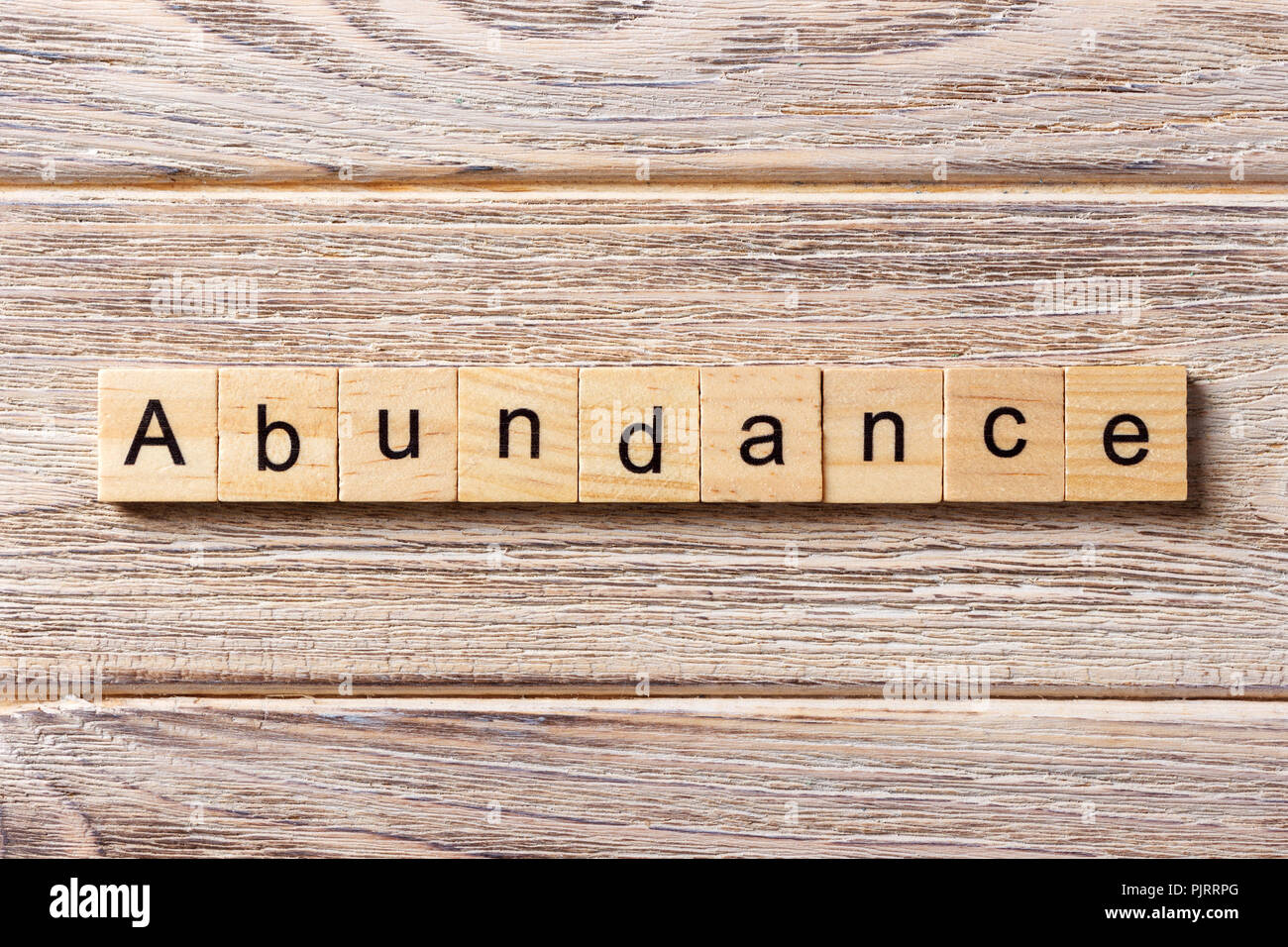 abundance word written on wood block. abundance text on table, concept. - Stock Image