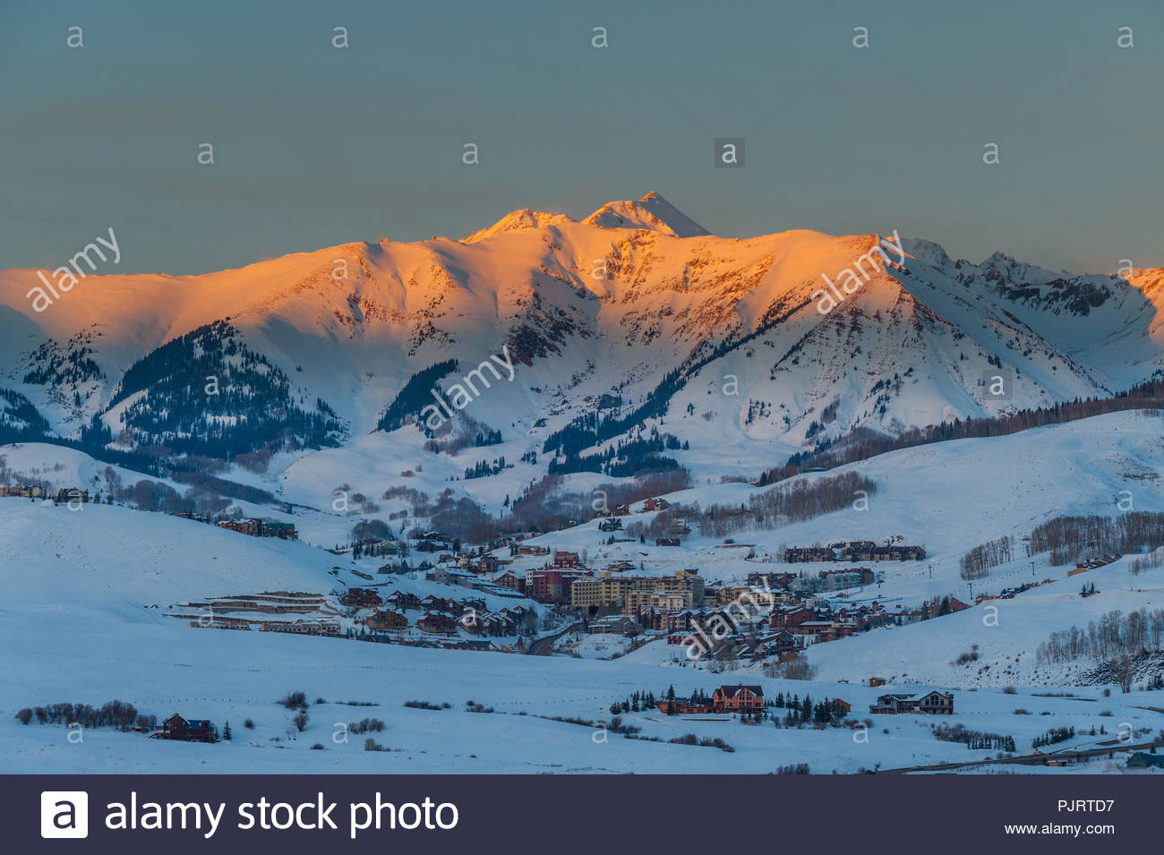Sunset light called alpenglow on Whiterock Mountain towering over the ski town of Mount Crested Butte, Colorado - Stock Image