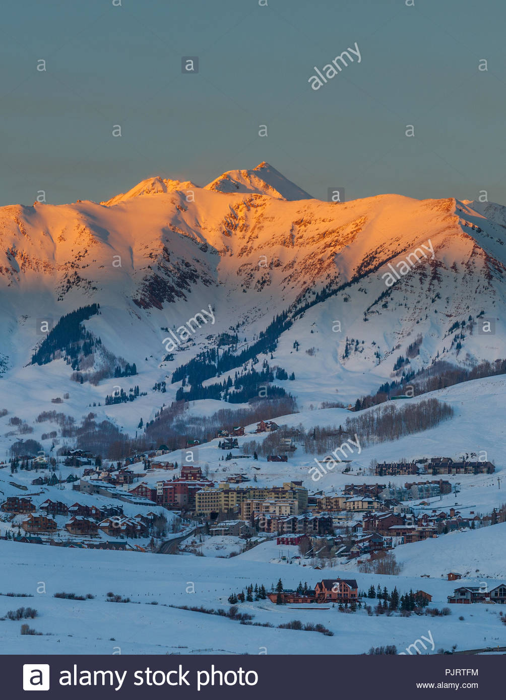 Sunset light called alpenglow shines on Whiterock Mountain towering over the town of Mount Crested Butte, Colorado, home of Crested Butte Mountain Res Stock Photo